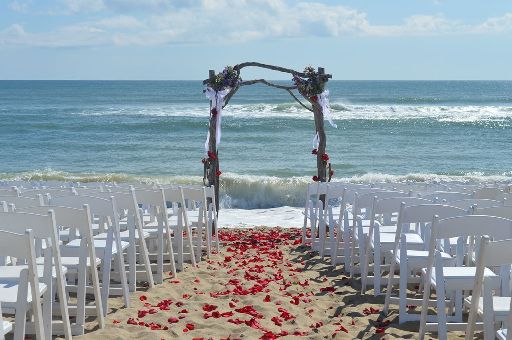 Martha's Vineyard oceanside beach wedding with arbor rose petals and white chairs