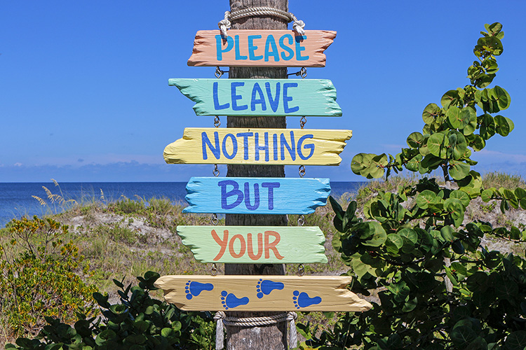 "Beach sign saying, ""Please leave nothing but your footprints."""