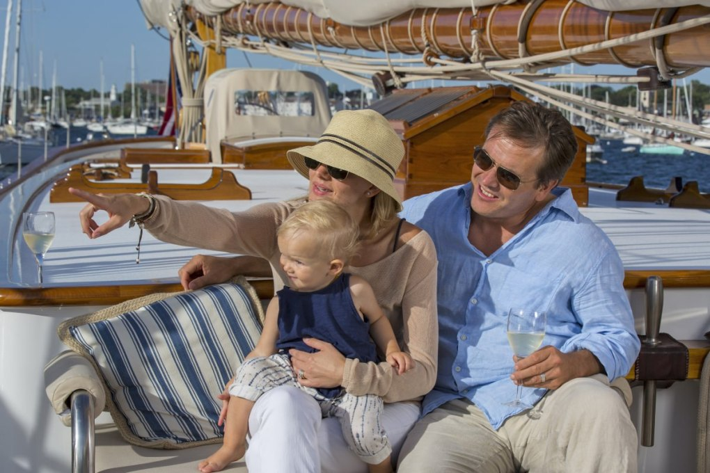 Wife, husband and baby lounging with champagne on the deck of the 141' sailing yacht COLUMBIA