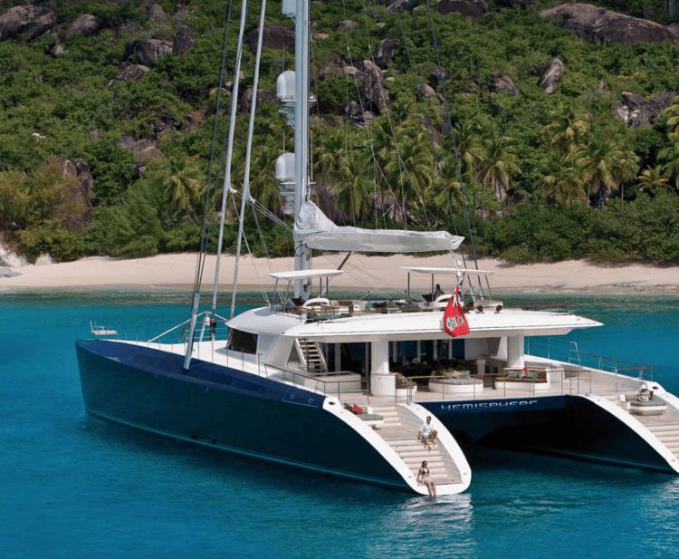 Yacht charterers sitting on the steps of the 145ft Pendennis sailing yacht catamaran HEMISPHERE off of Costa Rica. Operating in Central America, Australasia and other areas.