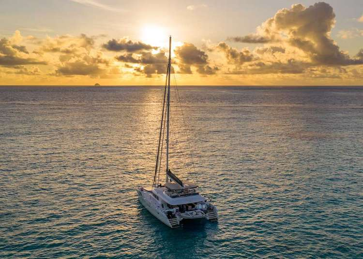 62ft Lagoon sailing catamaran TWIN FLAME on the water during golden sunset