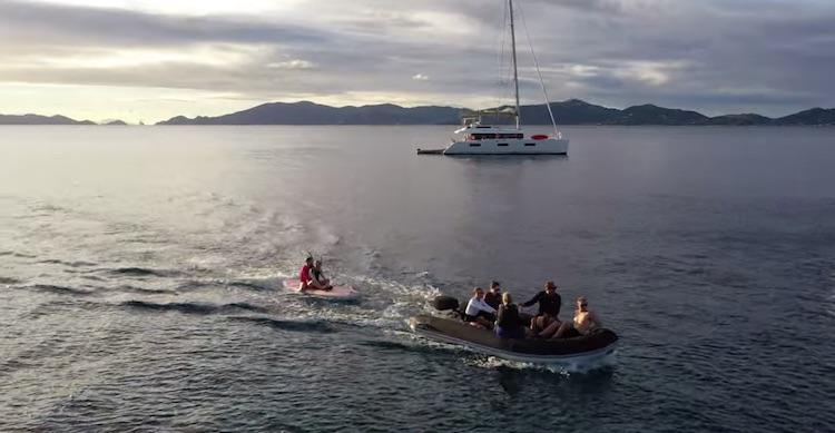 Dinghy towing a surfboard in the British Virgin Islands off 65ft sailing catamaran LOLALITA
