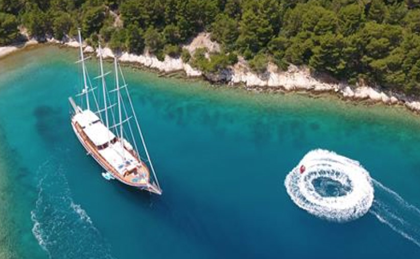 Aerial view of 112ft custom sailing yacht DOLCE VITA in lagoon with jet ski circle