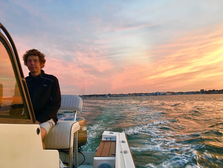 Captain Nick at the helm of the boat FamTrip at sunset on the Marblehead Harbor, Massachusetts