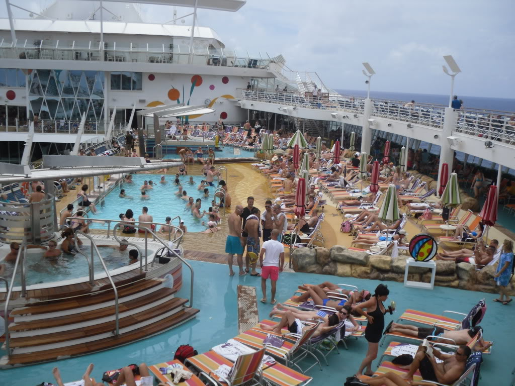 Cruise ship with crowded decks and pool on gray day. Photo©CarolKent