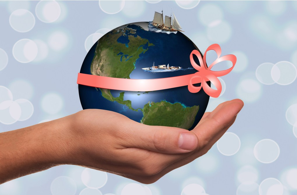 Earth with sailboat and motor yacht with coral ribbon in a hand for gift certificate