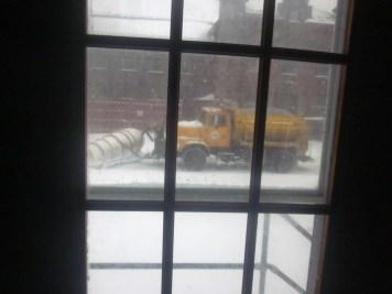 A snowplow truck seen through a door window.