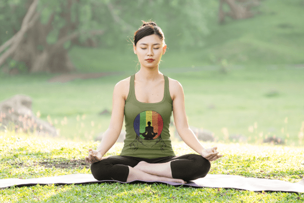 Image of a woman practicing yoga meditation outdoors wearing a unique design - bathing in the rainbow.
