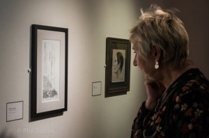 Image of a woman viewing Carolyn Murphy's printmaking monoprint at Warrington exhibition 2017