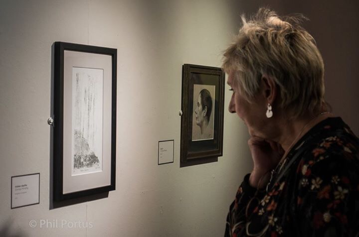 Image of a woman viewing artist Carolyn Murphy's monoprint 'Hidden Depths' at Warrington Contemporary Open 2017