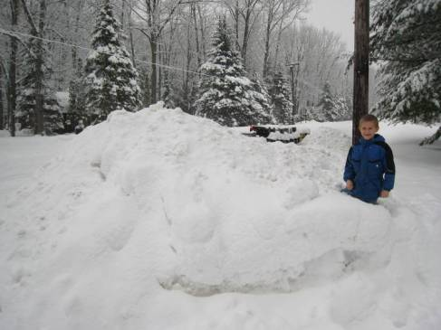 Zachary by the pile of snow at the end of our drive