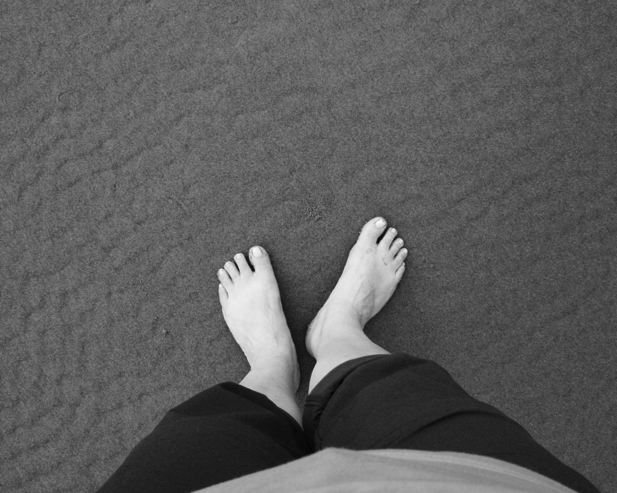 My feet on the beach. The sand had a really neat pattern from the waves.
