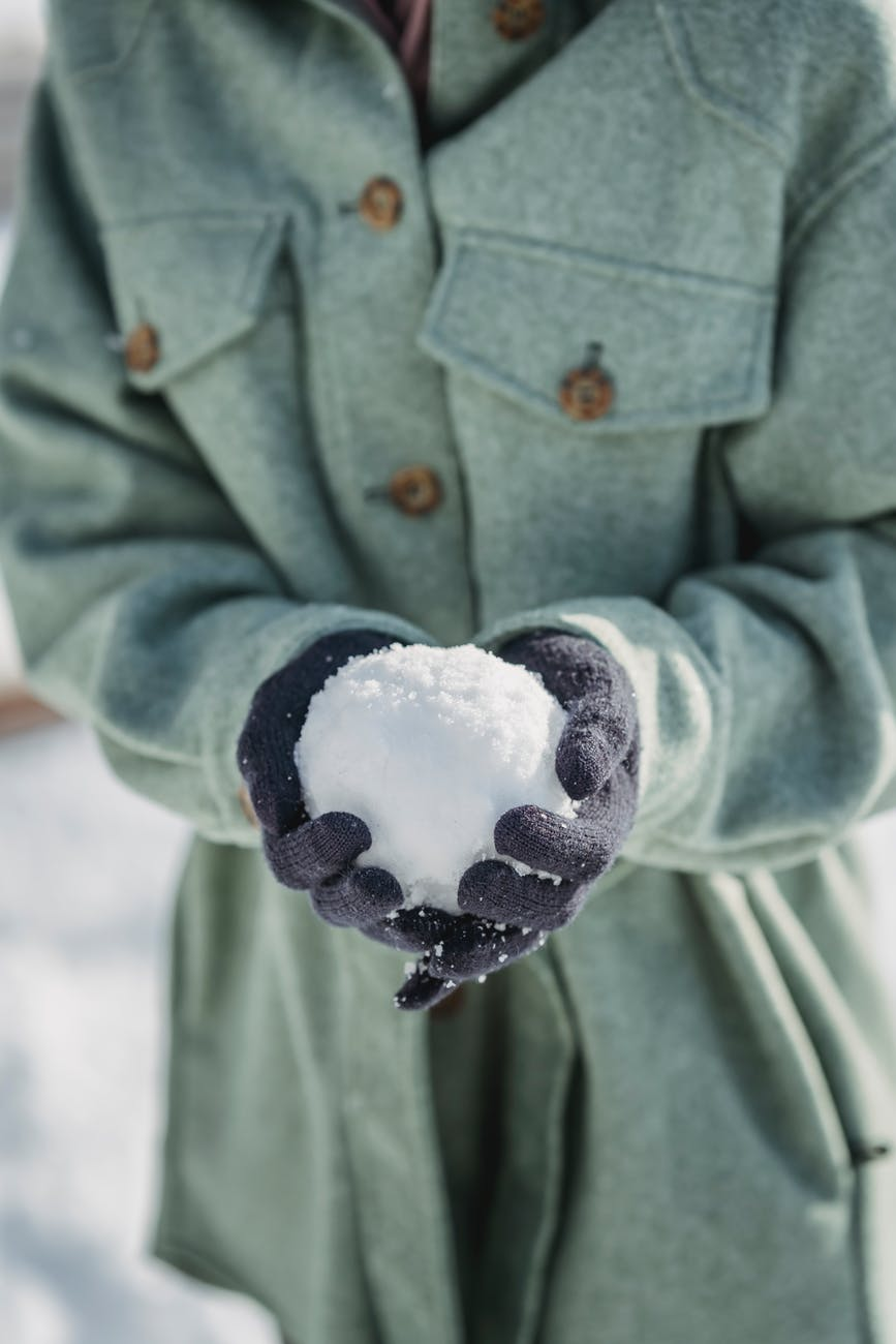 crop faceless woman holding snowball in winter park