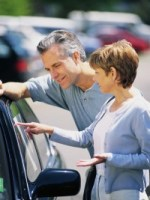 Couple Examining New Car for Sale