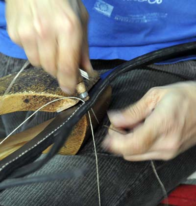 sewing leather by hand at the workshop of Angel Gonzalez