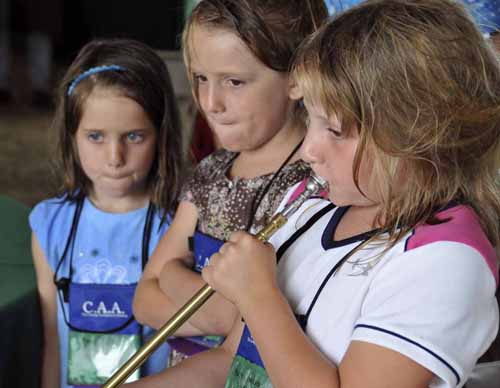 """the two girls not trying to play the horn are practising the """"pused lips"""" technique they were learning for blowing a coach horn"""