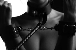 leather whip and a woman in handcuffs