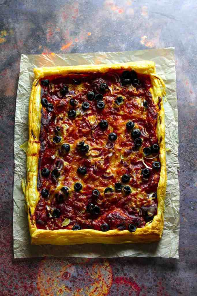 puff pastry pizza with pepperoni, olives, red onion