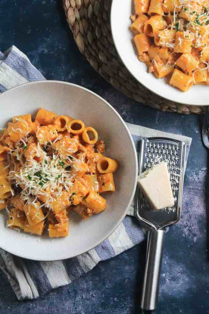 Rigatoni pasta with a creamy sausage and tomato sauce, in a pasta bowl with a chunk of parmesan and a cheese grater at the side