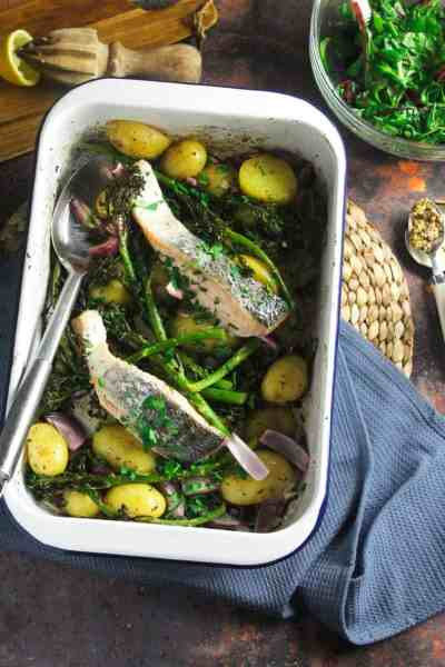 White enamel roasting dish containing two baked salmon fillets resting on sliced, roast baby potatoes, tenderstem broccoli and red onion.