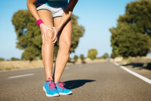 woman grabbing her knee in pain from running