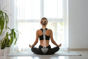 Young woman with good posture meditating at home