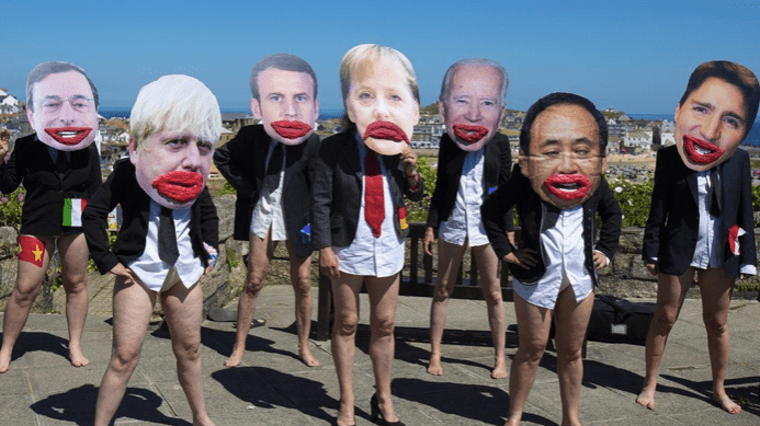 """Protesters demonstrating the G7 as """"all mouth and no trousers""""."""