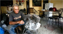 """Sergio Morales working on the engine of an old Harley-Davidson motorcycle in his dining room, where he does most of his restoration work. """"These engines are practically immortal,"""" he says. Credit Jose Goitia for The New York Times"""