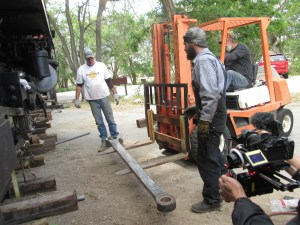 Dave drives the forklift while Forest and Pat help guide him.