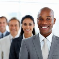 Happy African American business man with colleagues in a line