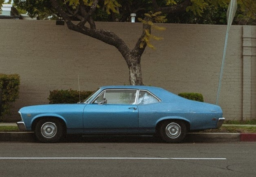A vintage blue car parked under the tree
