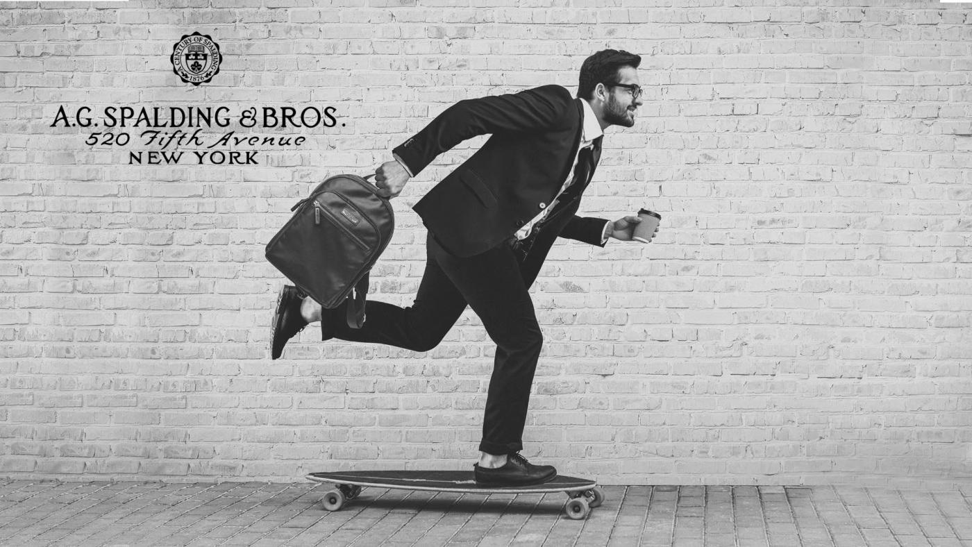 ragazzo su uno skateboard che va con una borsa Spalding & Bros a giro per la città - Cartoleria Rossi Mantova