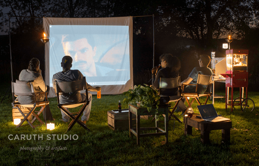 four adults watching a movie outdoors