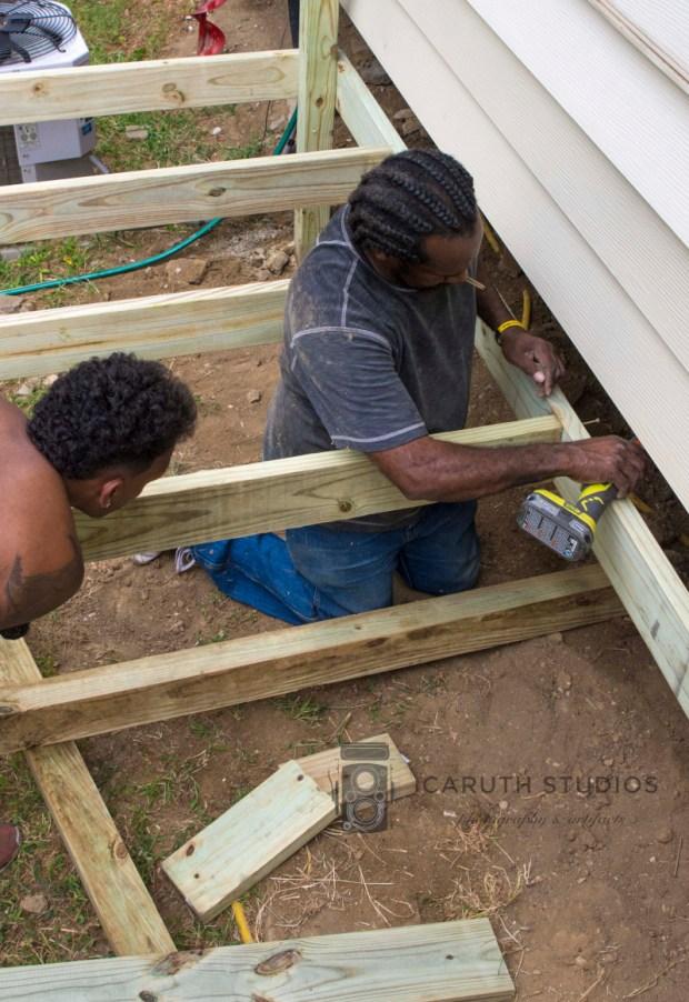 men placing cross beams for deck foundation