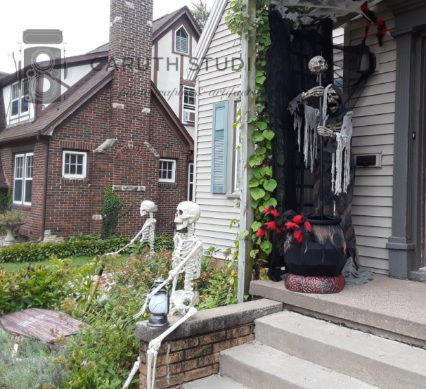 Skeleton on stoop laughing with a hanging lantern