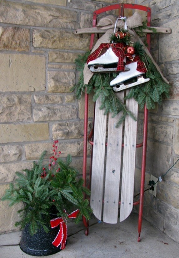 sled proped in the corner of a porch with evergreen plantings