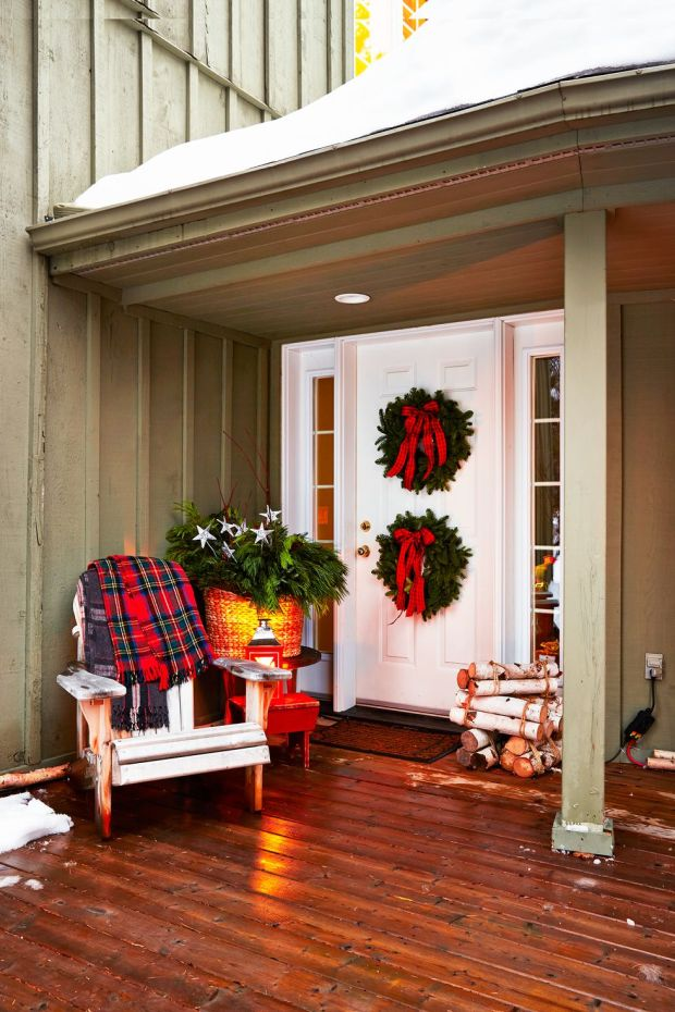 plaid and greenery around a white from door with wreaths