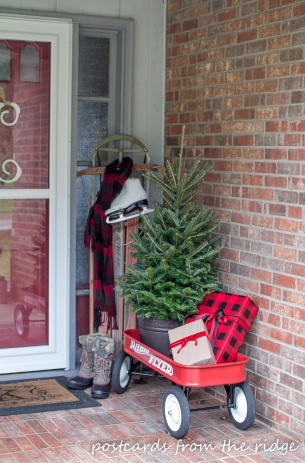 Sled and ice skates on a porch with a small evergreen tree and radio flyer wagon