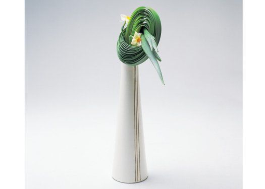 Ikebana moderno com vaso geométrico e folhas amarradas de forma circular