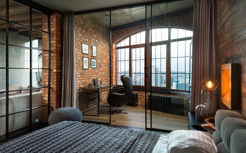 Loft com decoração rústica. Tijolos à vista combinados com madeira trazem aconchego para o ambiente. A grande janela traz a luz natural para o interior. Casa Ao Cubo. Foto: Martin Architects.