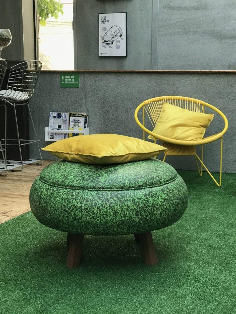 La Mainson Renault. Sala de Estar com grama sintética, pufe com estampa de grama e poltrona amarela.