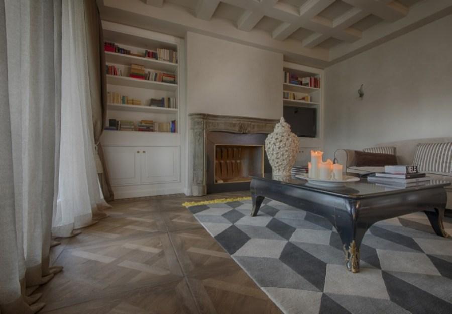 Pisos de madeira, madeira natural, parquet de madeira. Parquet Versailles. Sala em estilo clássico com piso em parquet de madeira versailles, lareira, estante com prateleiras para livros, sofá e mesa de centro. Casa ao Cubo.