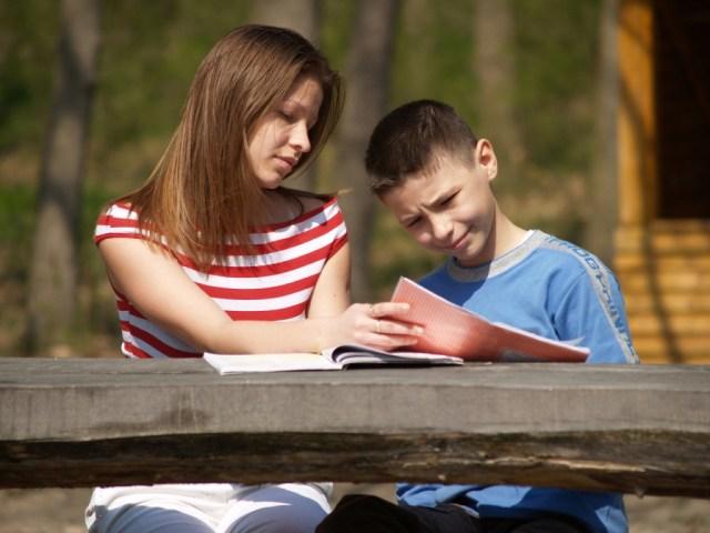Uma mulher e uma criança estão sentadas lado a lado em frente a uma mesa com alguns cadernos sobre a mesa. A mulher está explicando algo para a criança mostrando um dos cadernos.