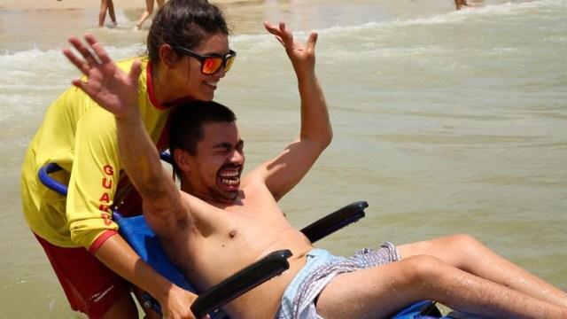 José Flávio entrou no mar usando uma cadeira anfíbia — Foto: Leonardo Sousa/Divulgação