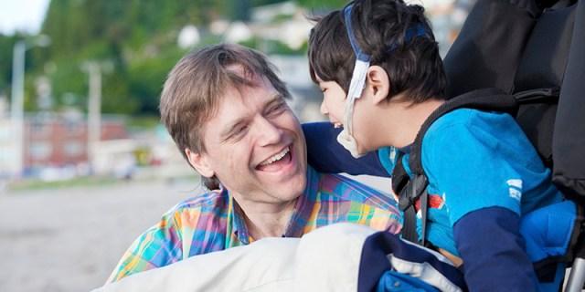 Um homem sorri ao lado de um garoto cadeirante que o abraça. O garoto também está sorrindo.