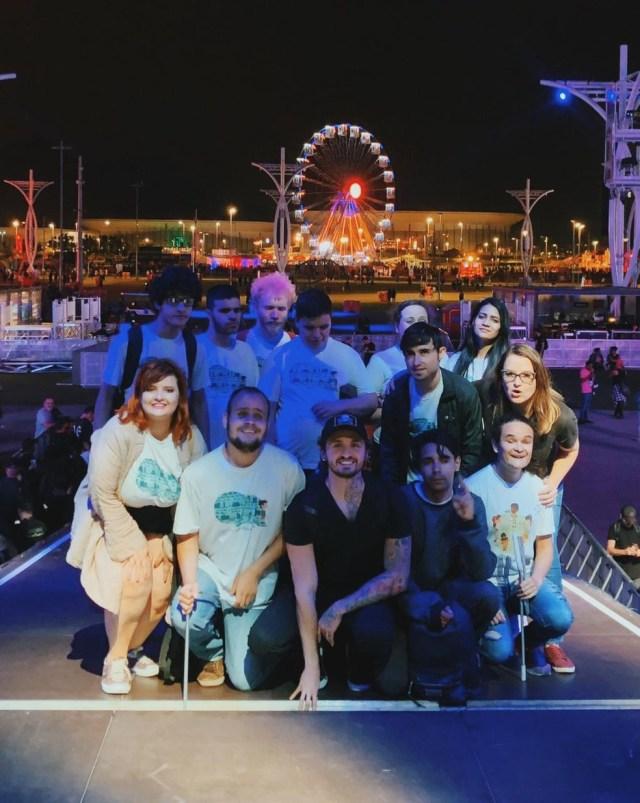 Pra cego ver: Foto mostra grupo de 13 pessoas que participou do teste do aplicativo Veever em palco do Rock in Rio na noite de terça-feira (24). Ao fundo, uma roda gigante e pessoas que trabalhavam na montagem do evento. — Foto: Veever/Divulgação