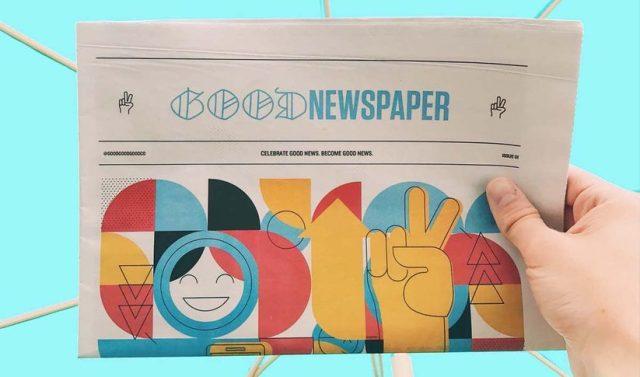 Uma mão segura um jornal chamado Good Newspaper em um fundo azul. A imagem no jornal é uma representação artística feito com formas geométricas coloridas vermelhas, azuis, amarelas e pretas. Entre elas, um rosto sorrindo e uma mão fazendo o símbolo da paz.