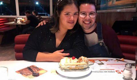 Foto de um casal de namorados, rapaz e moça, juntinhos, em uma mesa de restaurante. A sua frente, cardápios e uma banana split.