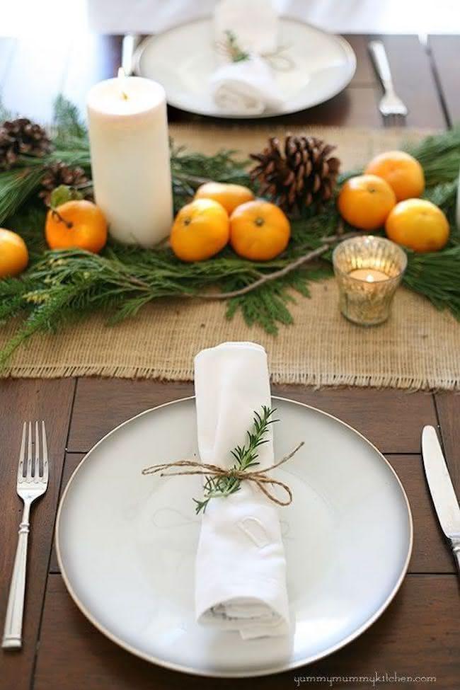 Centro de mesa com velas, frutas e pinhas