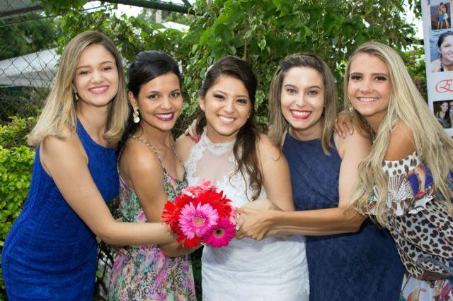 Noiva com amigas segurando o buquê